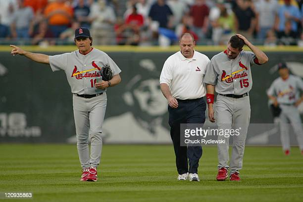 St Louis Cardinals' Center Fielder Jim Edmonds holds his head as he leaves the game with the help of the Cardinals' Trainer Edmonds hit his head on...