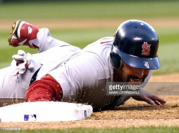 St Louis Cardinals' Fernando Vina dives safely back to first on a pick off attempt by Colorado Rockies' pitcher Aaron Cook 08 April 2003 at Coors...