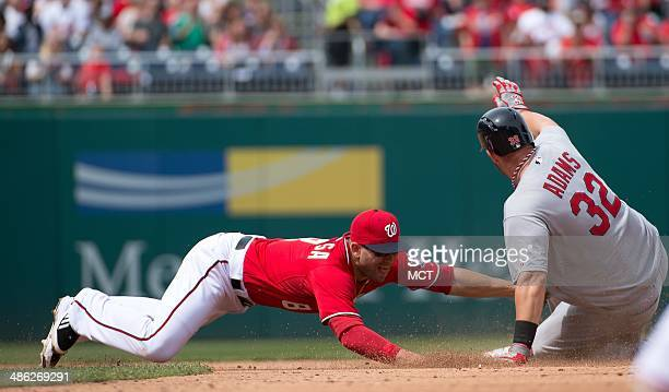 St. Louis Cardinals first baseman Matt Adams slides safely into second base ahead of the tag by Washington Nationals second baseman Danny Espinosa...