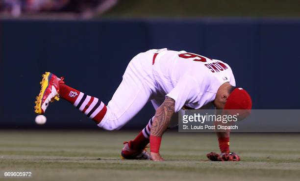 St Louis Cardinals infielder Kolten Wong gets turned around while trying to field a ball that was tipped by first baseman Jose Martinez against the...
