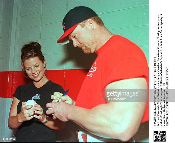 St Louis Cardinals'' Mark McGwire stops to sign a baseball for actress Yasmine Bleeth prior to a game with the Pittsburgh Pirates August 16 Bleeth of...