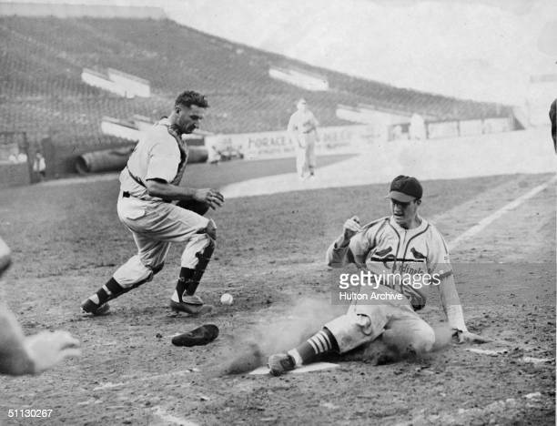 St Louis Cardinals outfielder Stan Musial slides into home plate to score a run as Boston Braves catcher Ernie Lombardi struggles for the ball during...