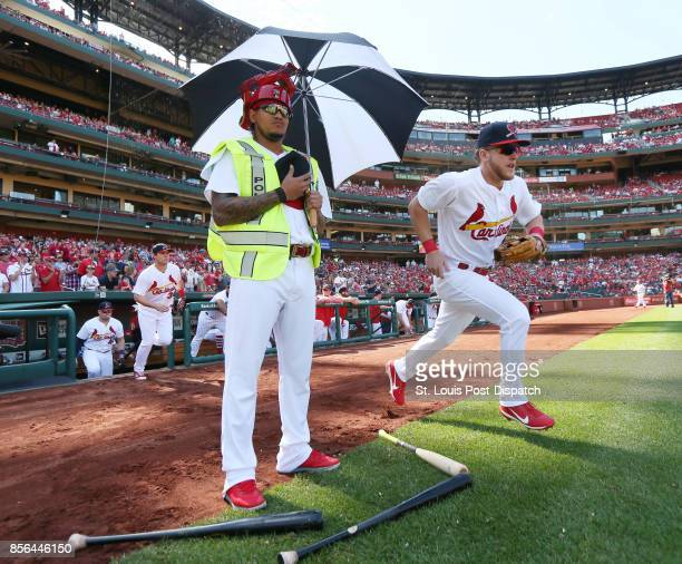 St Louis Cardinals pitcher Carlos Martinez remains on the edge of the grass as center fielder Harrison Bader and teammates take the field before a...