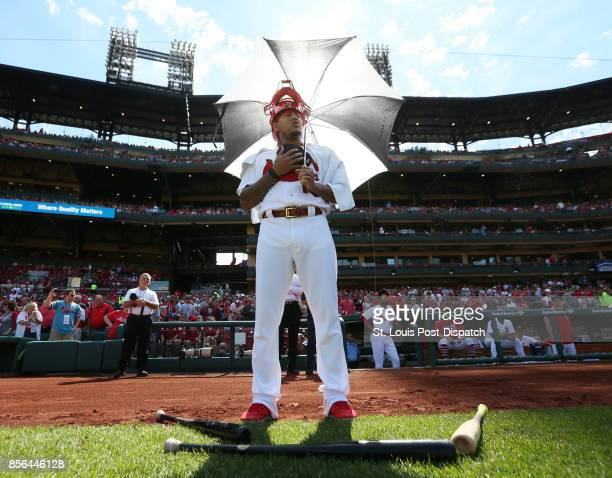 St Louis Cardinals pitcher Carlos Martinez settles in with an umbrella and catcher's mask as he partakes in a national anthem standoff against...