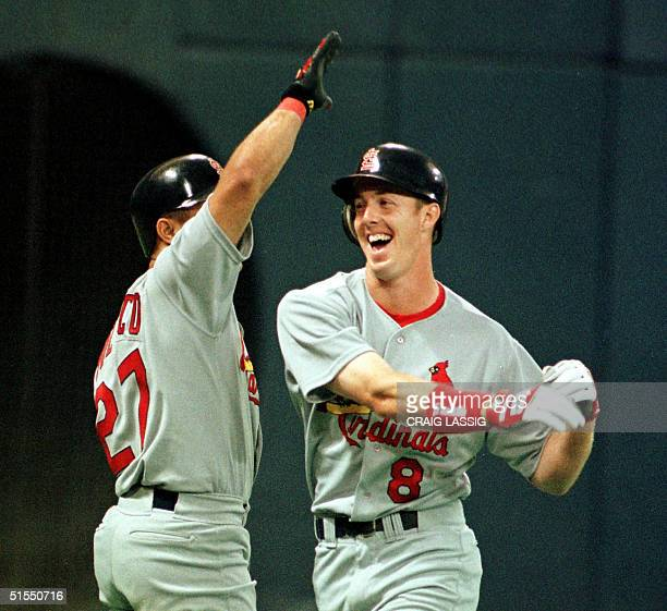 St Louis Cardinals rookie Chris Richard gives teammate Placido Polanco a high five after hitting a home run on the first pitch of his major league...