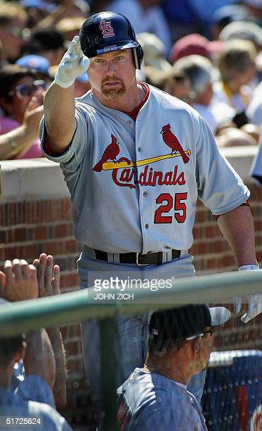 St Louis Cardinals slugger Mark McGwire salutes the team's owner in the stands on his return to the dugout after blasting his second homerun of the...
