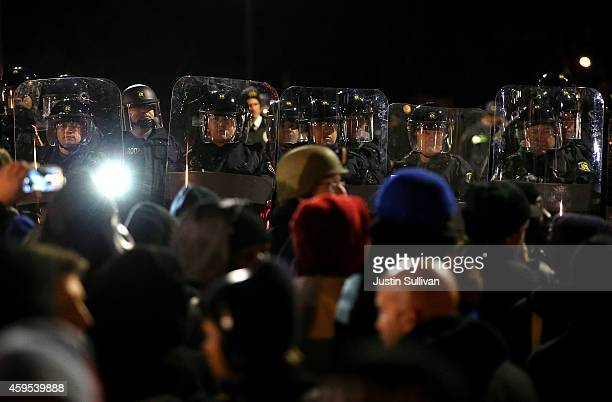 St Louis County police officers in riot gear stand guard in front of the Ferguson police department after a grand jury's decision was delivered on...