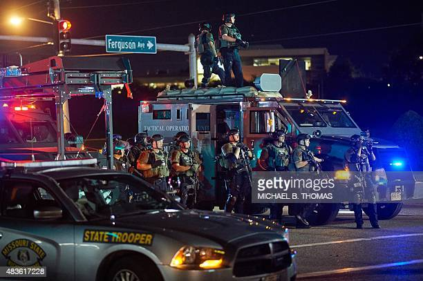 St Louis County Police officers outfitted in tactical equipment monitor the situation during a civil disobedience action on West Florissant Avenue in...