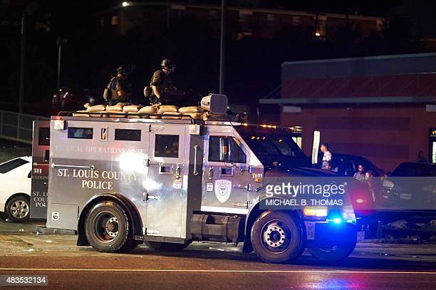 A St Louis County police officers respond in an MRAD vehicle after shots were fired during a protest march on August 9 2015 on West Florissant Avenue...