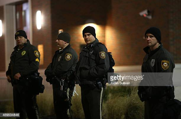 St Louis County police officers stand guard in front of the Ferguson police department on November 24 2014 in Ferguson Missouri A St Louis County...