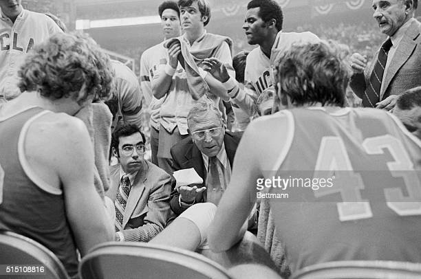 John Wooden UCLA basketball coach shown talking to his team during a time out and on the bench during his teams victory in the NCAA finals against...