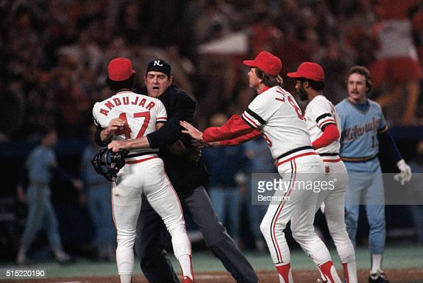 St Louis Cardinals pitcher Joaquin Andujar is restrained by the umpire during an argument with the Milwaukee Brewers Jim Gantner during the 7th game...