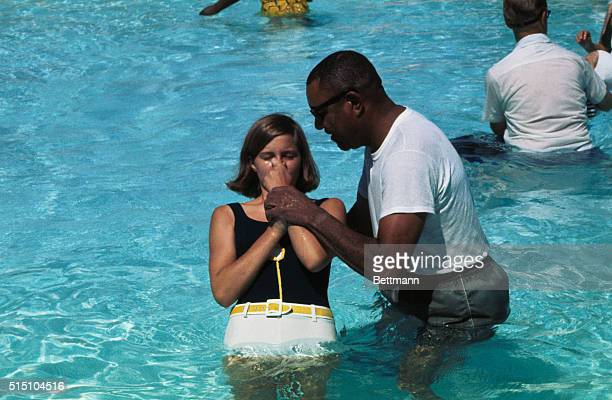 Miss Christine Cox Urbana IL is shown being baptized at a mass baptismal for Jehovah's Witnesses in Chain of Rocks Park by Brother Denver Carroll of...
