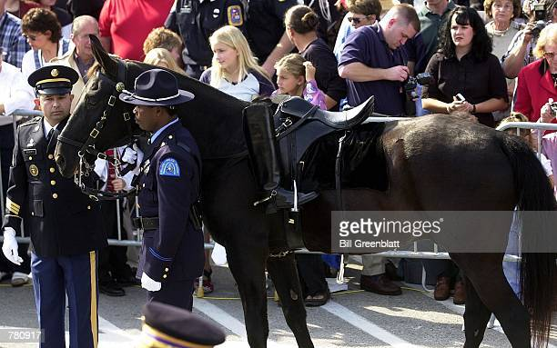 St Louis policeman holds the mount of a horse during a memorial service for the late Missouri Governor Mel Carnahan outside the state capital...
