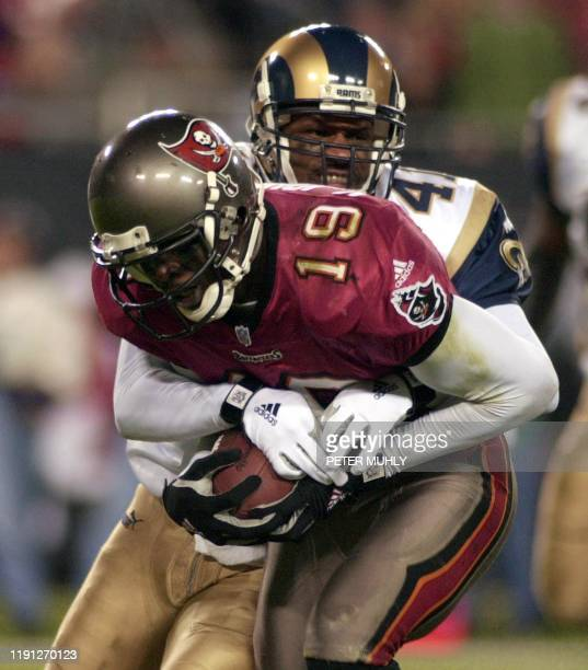 St Louis Ram Todd Lyght tries to strip the ball from Tampa Bay Buccaneer Keyshawn Johnson after a pass reception from Buccaneer quarterback Shawn...