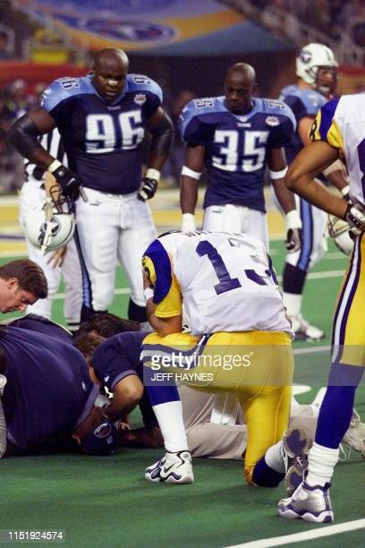 St Louis Rams quarterback Kurt Warner praying as Tennessee Titas safety Blaine Bishop is given aid during second half action in Super Bowl XXXIV at...
