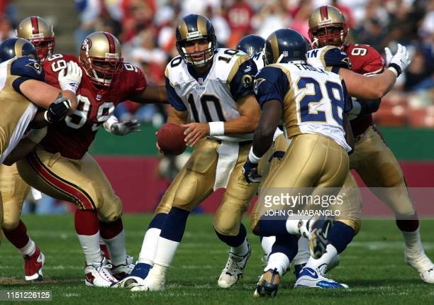 St Louis Rams' quarterback Trent Green handsoff to Rams' runningback Marshall Faulk as San Francisco 49ers' defensive tackle Brentson Buckner moves...
