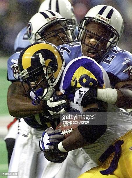 St Louis Rams running back Marshall Faulk is wrapped up by Tennessee Titans safety Steve Jackson during first half action in Super Bowl XXXIV at the...