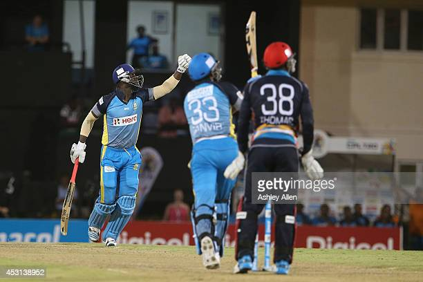 St Lucia Zouks captain Darren Sammy celebrates as Sohail Tanvir and Devon Thomas look on during a match between St Lucia Zouks and Antigua Hawksbills...