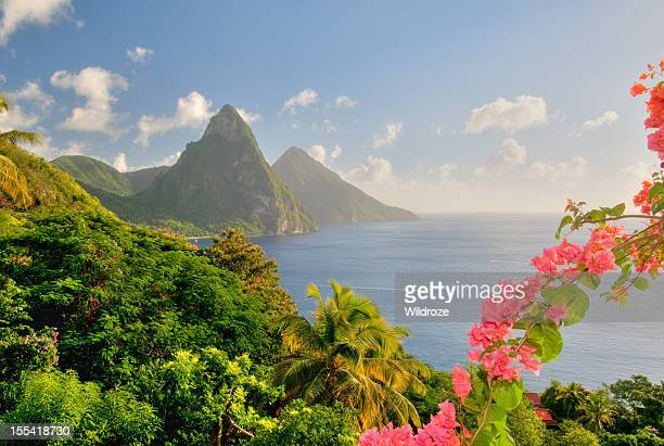 st. lucia's twin pitons lit by sunset glow - st. lucia stock pictures, royalty-free photos & images