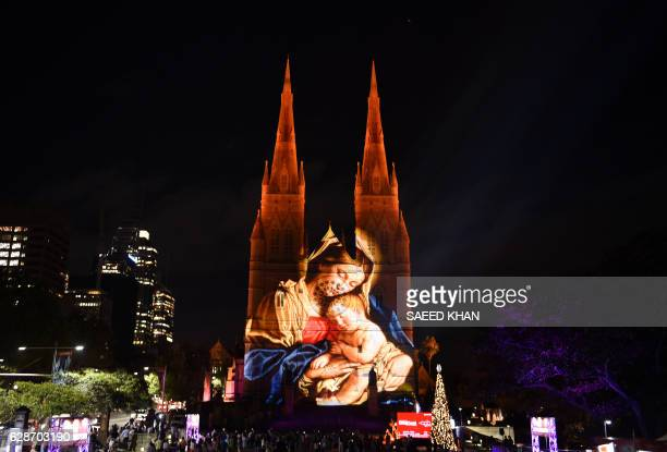 TOPSHOT St Mary's Cathedral is illuminated with a Christmasthemed projection in Sydney to celebrate the Christmas season on December 9 2016 / AFP /...