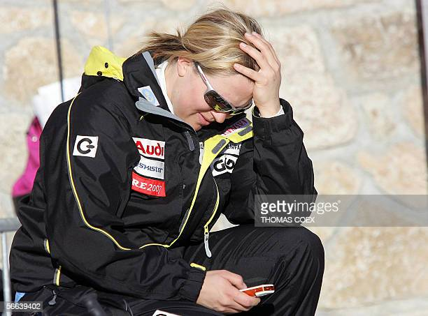 Sweden's Anja Paerson reads a SMS on her mobile phone after the Alpine skiing World Cup women's Downhill race in St Moritz 21 January 2006 Austria's...