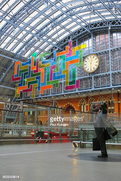 St Pancras International station interior. Stained glass panels called Chromolocomotion by David Batchelor in the series Terrace Wires and the statue...