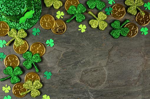 St Patricks Day corner border of shamrocks, gold coins & leprechaun hat over a dark background 1124856490