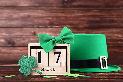 St. Patrick's Day. Green hat with clover leafs, wooden calendar and bow tie 1129109982