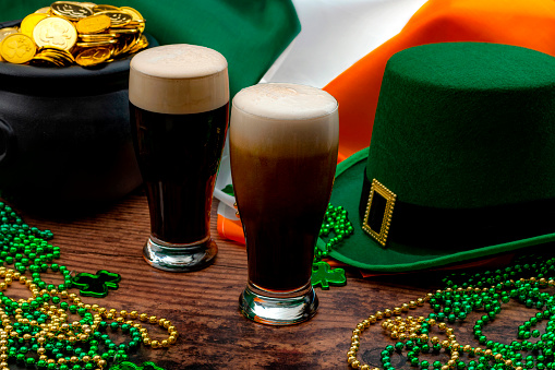 St Patrick's day party and Irish celebration of patron saint concept theme with frothy glasses of dry stout, green hat with a buckle, a pot of gold, the flag of Ireland and beads with shamrock in a pub 1135596773