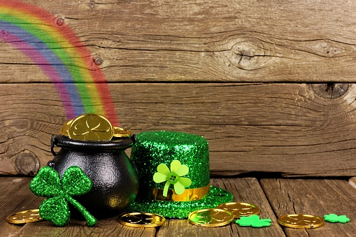 St Patricks Day Pot of Gold with rainbow & decor against wood 910707526