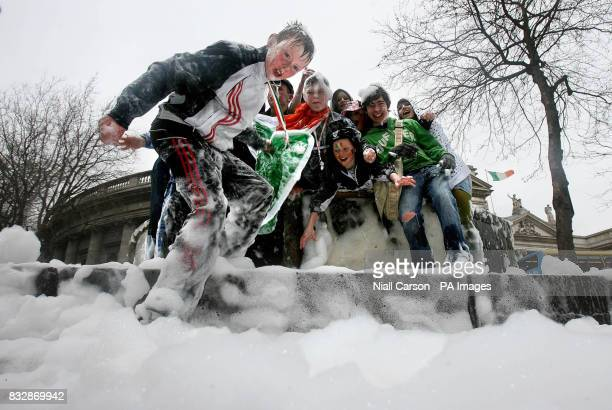 St Patrick's Day revellers hold an impromptu foam party in a fountain on College Green, Dublin, after a bottle of washing up liquid was poured into...