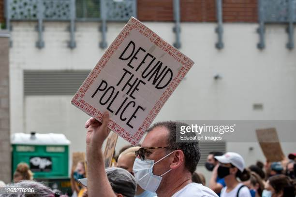 St. Paul, Minnesota, No police in our schools protest, Protester marching with defund the police sign.