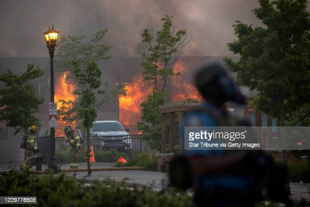 Firefighters battle the flames of a business along University Avenue as riot officers police the street Protesters had spread to both of the Twin...