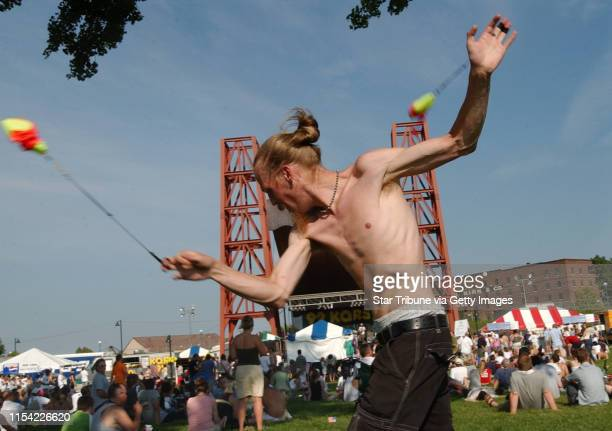 St Paul Mn Weds July 2 2003Cody Harland of Minnetonka plays poi a Malaysian game to the sounds of Big Wu the band playing on the stage in the...