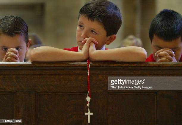8 yr old Isaiah Counts of Holy Acadamy was pensive with his rosary during prayer as classmates had their own prayers going both of Holy Family...