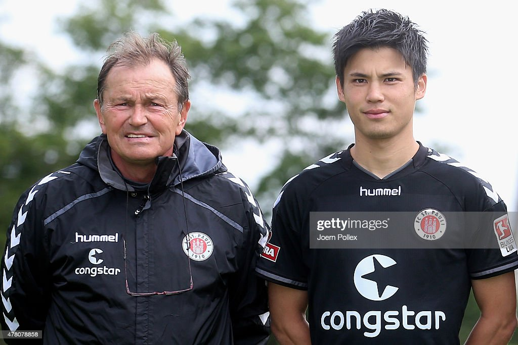 St. Pauli Football Club's new signing Ryo Miyaichi (R) and head coach Ewald Lienen pose for a photograph following his transfer on June 22, 2015 in Hamburg, Germany.