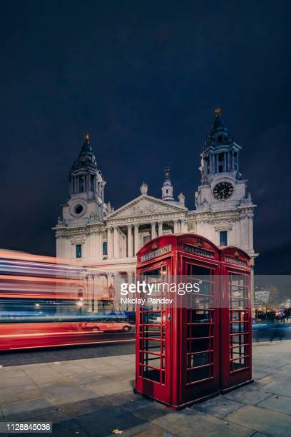 st paul's cathedral at night with blurred red bus and traditional london telephone booths - red telephone box stock pictures, royalty-free photos & images