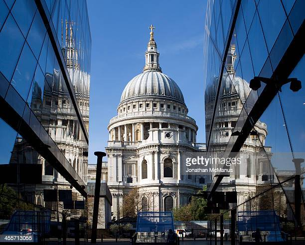 CONTENT] St Paul's cathedral with two partial reflections either side of it in the glass of the shopping centre in Cheapside There is a blue sky