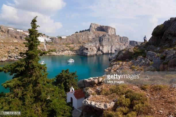 st pauls harbour, beach and acropolis, lindos rhodes greece - lindos stockfoto's en -beelden