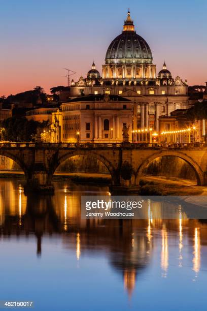st. peter's basilica and tiber river illuminated at dusk, rome, lazio, italy - vatikan stock-fotos und bilder