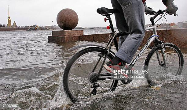 A boy rides a bicycle along the flooded Neva river embankment in St Petersburg 29 October 2006 AFP PHOTO/ ALEXANDER TARAN
