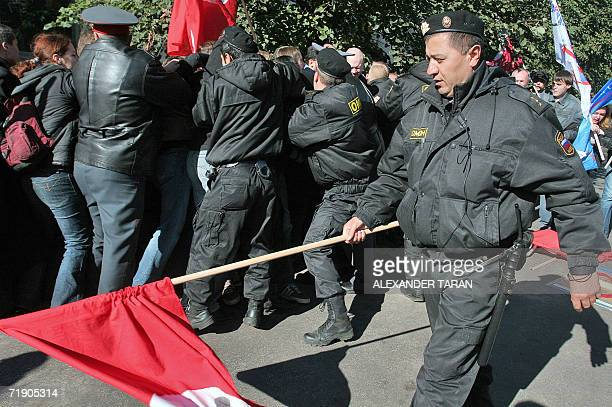 Russian special police forces officer carries a red flag as his colleagues arrest a participants of human rights defence rally devoted to the summit...