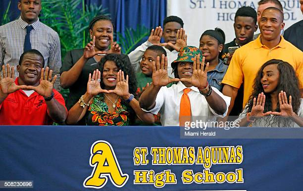 St Thomas Aquinas' Michael Irvin Jr makes the U sign with his family as he signs with the University of Miami on National Signing Day at Saint Thomas...