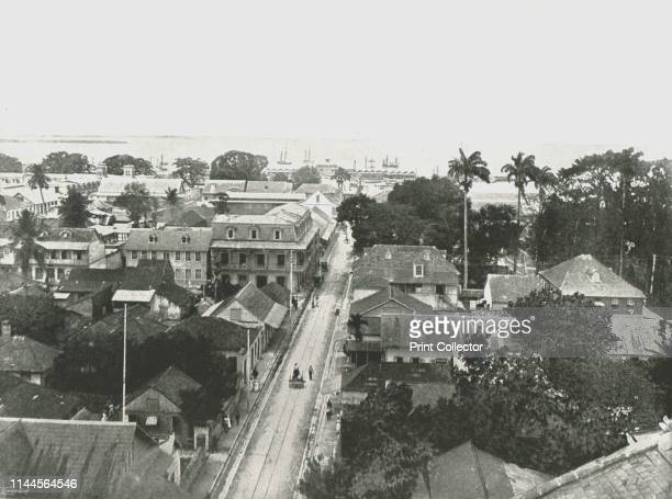 """St Vincent Street, Port of Spain, Trinidad, 1895. View of the town with ships on the Caribbean beyond. From """"Round the World in Pictures and..."""
