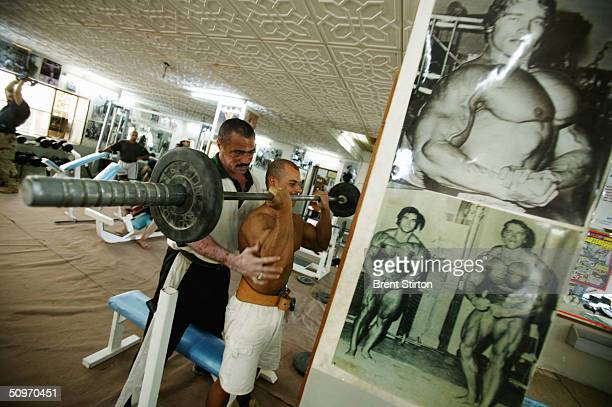 Staar Atya Radi Iraqi national youth champion lifts weights as Hamid Abd AlRahman a national trainer spots him during a workout at the Arnold Classic...