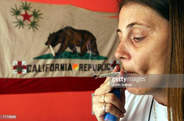 Staarla Heaney smokes a marijuana cigarette in front of the California state flag at the San Francisco Patients Cooperative a medical cannabis...