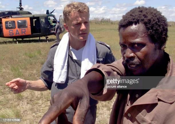 Stabsarzt Thomas Harbaum unterhält sich am 832000 bei einem ungeplanten Notstop des Hubschraubers im freien Buschgelände südlich vom Stützpunkt Beira...
