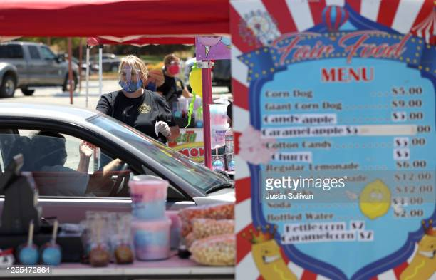 Stacee Hoffee helps a customer during a drivethru food fair in the parking lot at the Veterans' Memorial Auditorium on July 10 2020 in San Rafael...