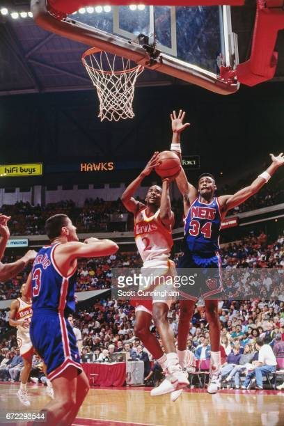 Stacey Augmon of the Atlanta Hawks shoots against the New Jersey Nets during a game played circa 1990 at the Omni in Atlanta Georgia NOTE TO USER...